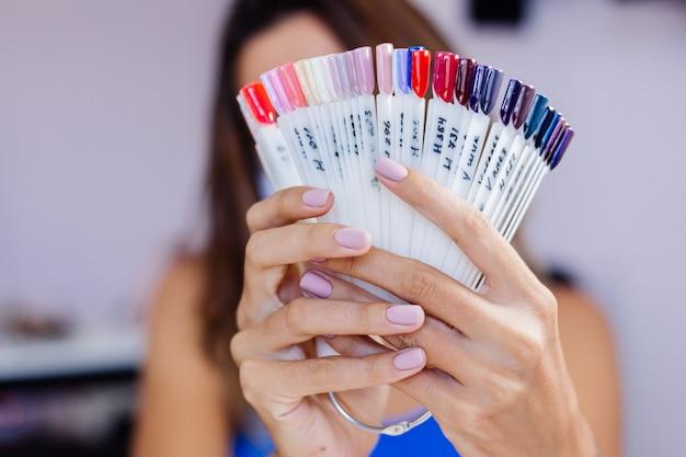 Frau in schützender medizinischer maske im schönheitssalon halten palette und wählen sie eine farbe maniküre-verfahren nagelpflege feierliche eröffnung quarantäne ist vorbei kleinunternehmerin sind wieder offen