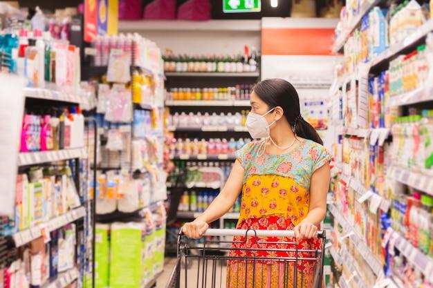 Frau in schutzmaske beim einkaufen im supermarkt während der coronavirus-quarantäne