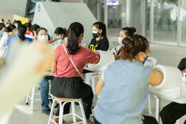 Frau in schutzmaske, die blutdruck und herzfrequenz überprüft