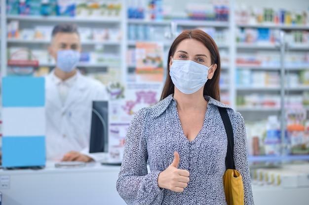 Frau in schutzmaske, die eine ok geste zeigt