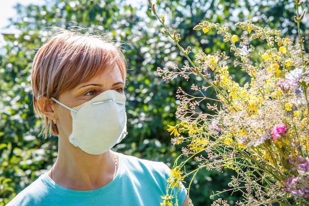 Frau in schutzmaske, die einen strauß wildblumen hält und versucht, allergien gegen pollen zu bekämpfen. allergie-konzept.
