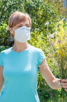 Frau in schutzmaske, die einen strauß wildblumen hält und versucht, allergien gegen pollen zu bekämpfen. frau, die ihre nase vor allergenen schützt. allergie-konzept.