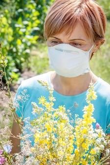 Frau in schutzmaske, die einen strauß wildblumen hält und versucht, allergien gegen pollen zu bekämpfen. natürlicher hintergrund. allergie-konzept.