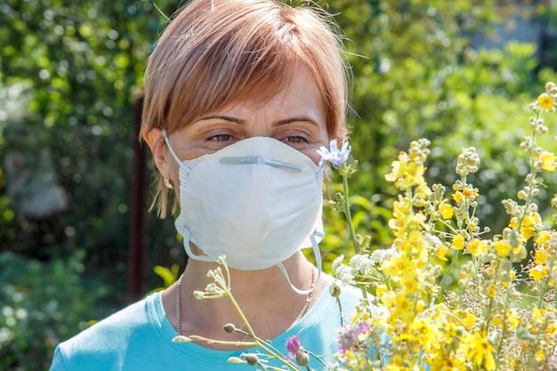 Frau in schutzmaske, die einen strauß wildblumen hält und versucht, allergien gegen pollen zu bekämpfen.