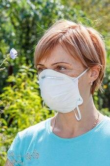 Frau in schutzmaske, die versucht, allergien gegen pollen zu bekämpfen.
