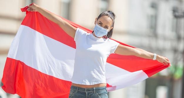 Frau in schutzmaske hält an einem sonnigen tag im freien eine flagge österreichs hinter sich.