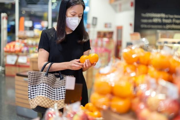 Frau in schutzmaske kauft orangenobst-supermarkt