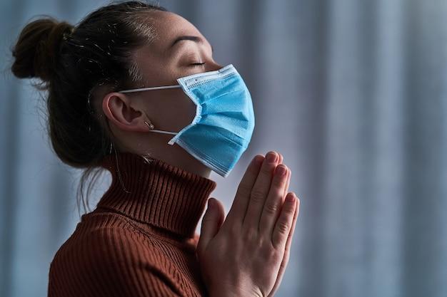 Frau in schutzmaske mit geschlossenen augen und betenden händen bittet gott um heilung und genesung während der krankheit