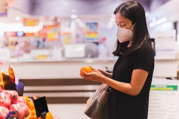 Frau in schutzmaske mit orangenobst-supermarkt