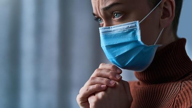 Frau in schutzmaske mit traurigen augen und betenden händen, bittet gott um heilung und genesung während der krankheit