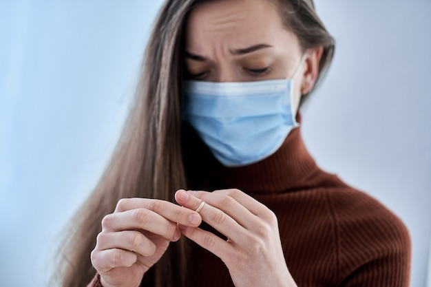 Frau in schutzmaske ring vom finger entfernen. trennung der beziehung nach dem zusammenleben und aufenthalt zu hause mit dem ehemann in quarantäne und isolation aufgrund einer coronavirus-epidemie. scheidungskonzept