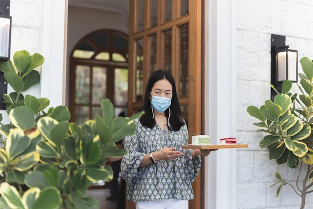 Frau in schutzmaske serviert dem kunden ein stück kuchen auf einem tablett