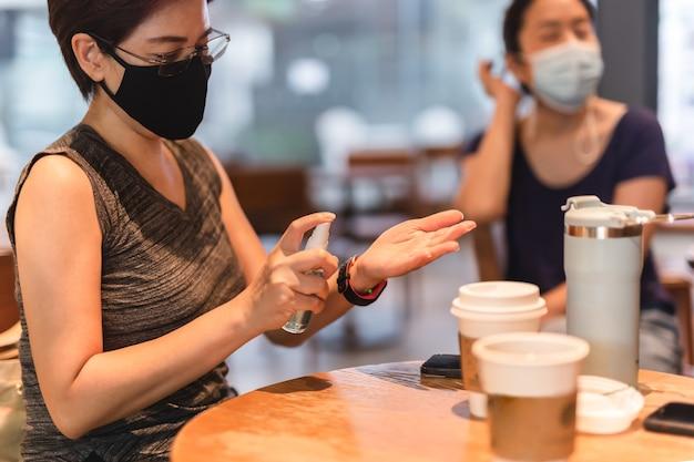 Frau in schutzmaske sprühen sie ihre hände mit antiseptischem spray im café ein