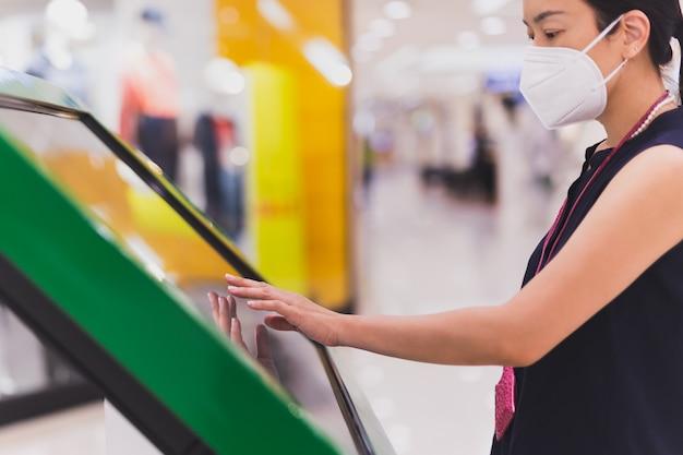 Frau in schutzmaskenhand verwendet digitalen touchscreen, um informationen zu erhalten