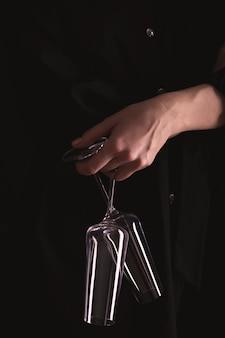 Frau in schwarz hält zwei weingläser