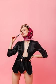 Frau in schwarzer robe und schal trägt puder auf ihr gesicht auf
