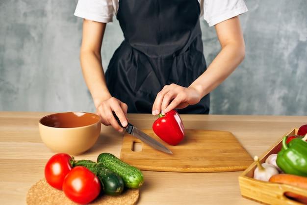 Frau in schwarzer schürze, die gesundes essen schneidebrett kocht