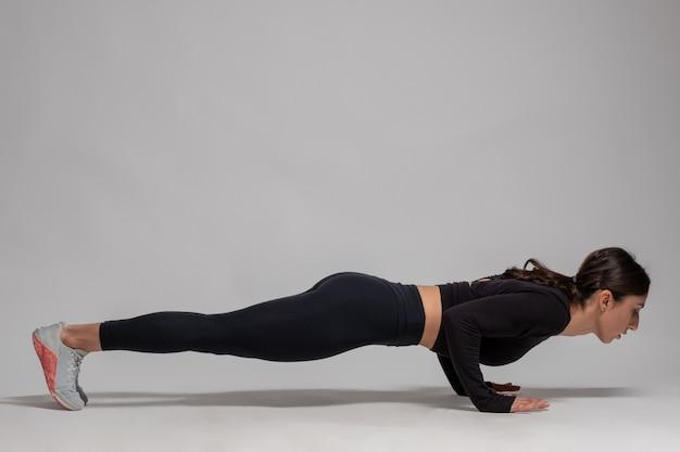 Frau in schwarzer sportkleidung macht liegestütze an grauer wand