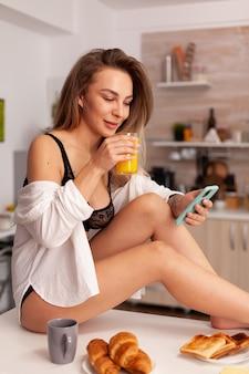 Frau in sexy unterwäsche, die auf dem smartphone surft, das auf dem küchentisch sitzt und ein glas frischen orangensaft hält. verführerische frau mit tätowierungen mit telefon, die morgens temping-unterwäsche trägt.