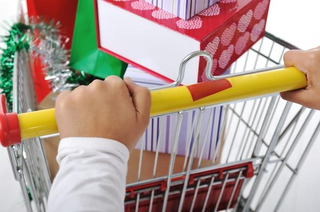Frau in shoping drückenden warenkorb mit taschen und boxen