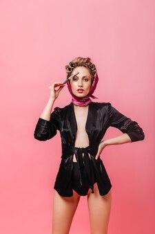 Frau in shorts, bademantel und schal hält pinsel für make-up