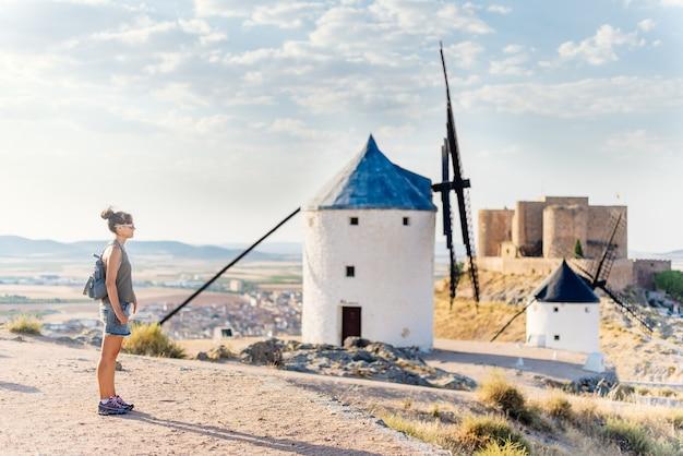 Frau in sommerkleidung, sonnenbrille und tasche steht neben einigen alten windmühlen und einem schloss in consuegra, spanien.
