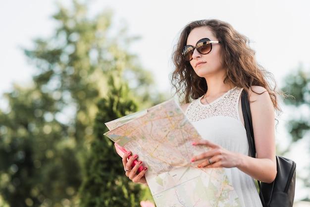 Frau in sonnenbrille mit karte