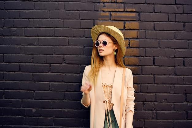 Frau in sonnenbrille und dekorationshut spazieren im freien backsteinmauer im hintergrund.