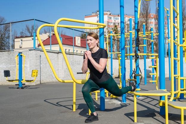 Frau in sportbekleidung, die mit trx-ausrüstung arbeitet, die beine im freien ausübt. frauentraining für einen gesunden lebensstil.