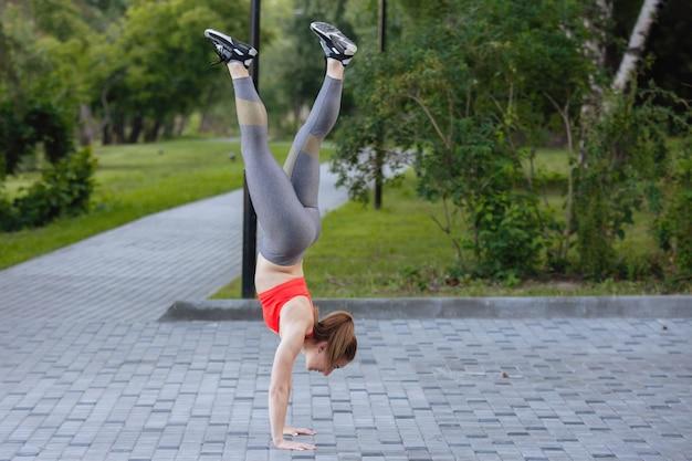 Frau in sportbekleidung steht in einem fitnessstudio in einem sommerstadtpark auf ihren händen.
