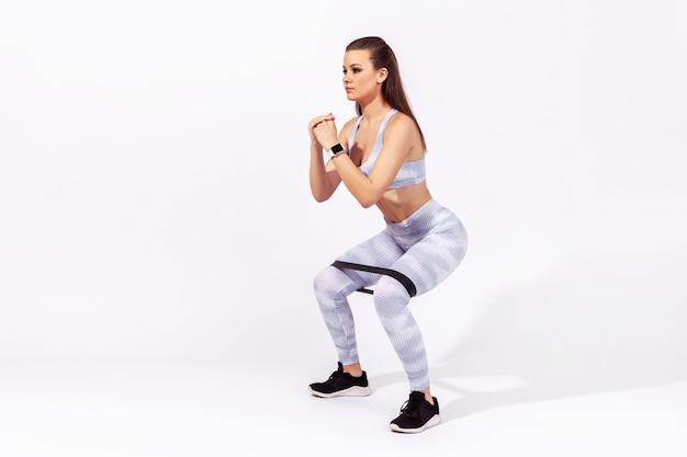Frau in sportkleidung macht kniebeugen mit widerstandsband an den knien, pumpt beine und gesäßmuskeln