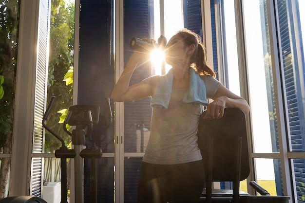 Frau in sportkleidung trinkwasser aus der flasche im fitnessstudio. es gibt sonnenlichtstrahl von moning im hintergrund.