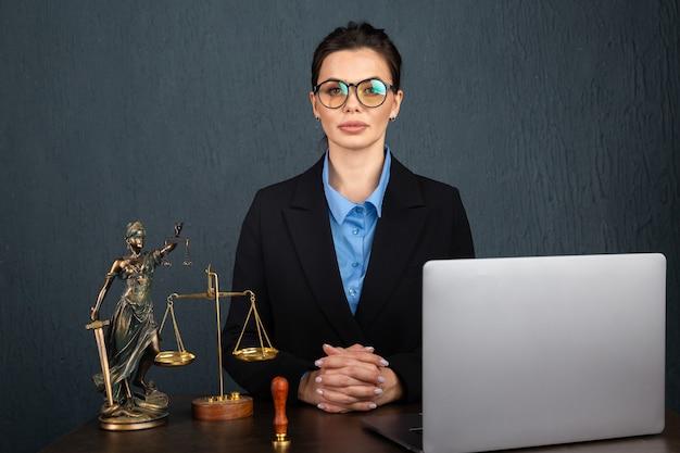 Frau in stilvollen gläsern, die notar im lehrbuch während des online-lernens auf laptop schreiben