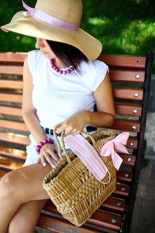 Frau in strohhut und tasche mit rosa schutzmaske, sitzend in der bank im park im freien in der stadt, konzeptselbstpflege, leben während der coronavirus-pandemie, covid-19.