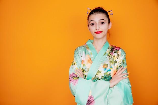Frau in traditionellem japanischem kimono mit skeptischem ausdruck, der vor unmut einen schiefen mund macht, der die hände auf ihrer brust auf orange kreuzt