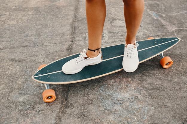 Frau in turnschuhen, die skateboard im freien auf asphaltoberfläche reiten.