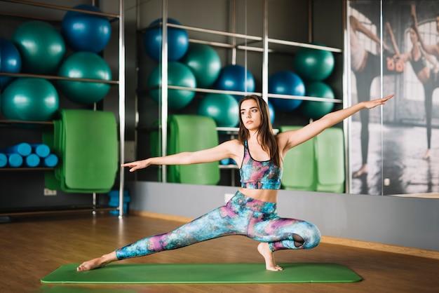 Frau in übendem yoga der sportkleidung in der turnhalle