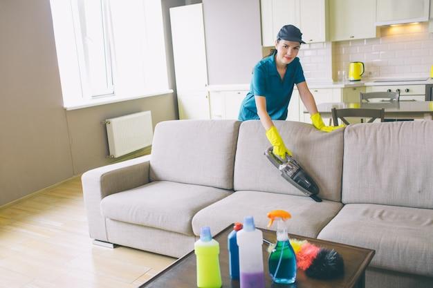 Frau in unform steht hinter sofa und säubert es mit kleinem staubsauger