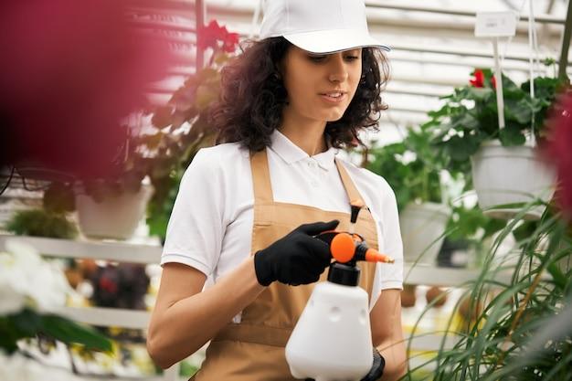 Frau in uniform, die bunte blumen im gewächshaus gießt