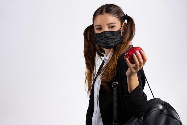Frau in uniform mit einem roten apfel eine maske auf weißer wand leeren seitenraum