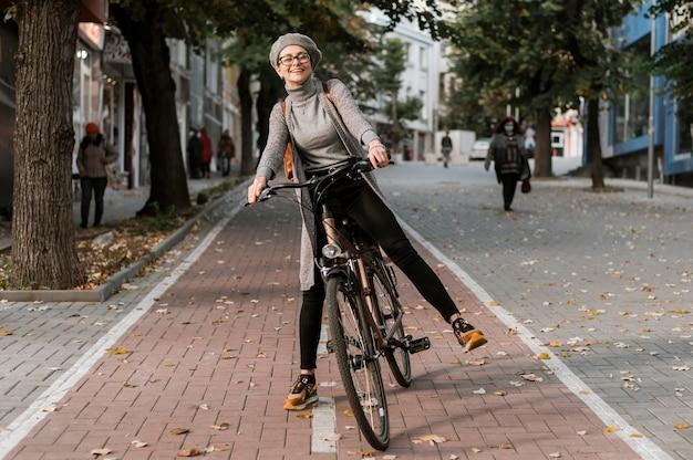Frau in voller körpergröße, die das fahrrad reitet