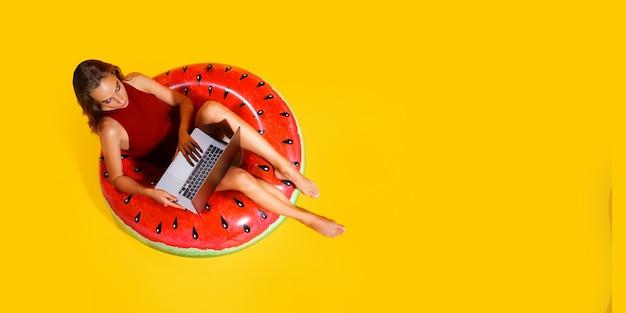 Frau in voller länge im roten badeanzug sitzt in aufblasbarem wassermelonenring mit laptop-pc auf gelbem hintergrund. passagierreisen ins ausland wochenendausflug. flugreisekonzept. ansicht von oben