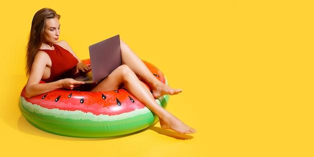Frau in voller länge im roten bikini sitzt in aufblasbarem wassermelonenring und benutzt laptop-pc einzeln auf gelbem hintergrund. passagierreisen ins ausland wochenendausflug. flugreisekonzept.