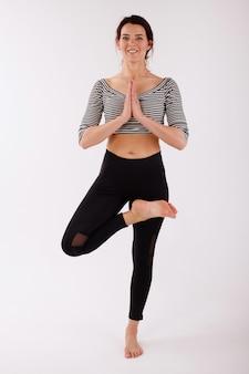 Frau in vrikshasana position auf einem weißen hintergrund im studio. yoga und meditation machen. schwarze sportgamaschen und top. internationaler yogatag