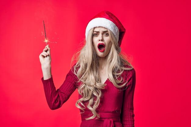 Frau in weihnachtskleidung wunderkerzen emotionen mode roten hintergrund