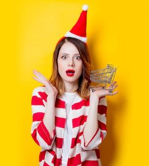 Frau in weihnachtsmann mütze mit supermarkt warenkorb
