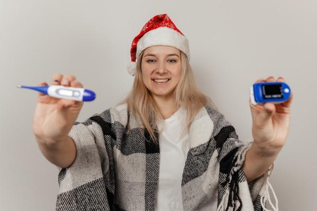 Frau in weihnachtsmütze und wickel hält thermometer und pulsoximeter auf grauem, isoliertem hintergrund