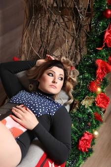 Frau in weihnachtsschmuck mit einem buch. mädchen liest ein buch in der nähe der blumen