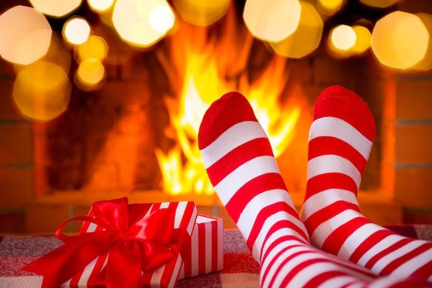 Frau in weihnachtssocken nahe kamin. person, die sich zu hause entspannt