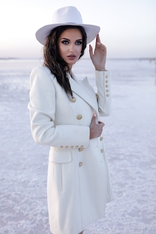 Frau in weiß frauen mit winterschuhen europäisches mädchen im mantel, das an einem kalten tag lächelt fröhliche blondhaarige frau, die spaß während des winterfoto-shootings wintersee über schneewarmen stiefeln hat